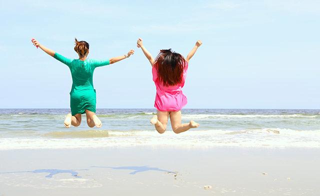 海でジャンプする女性2人