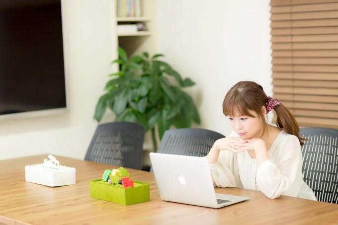 一人でパソコンの前に座る女性