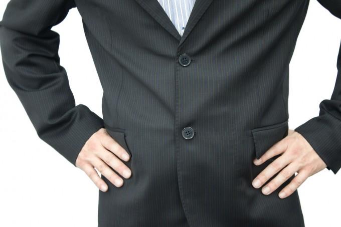 腰に手を当てたスーツ姿の人