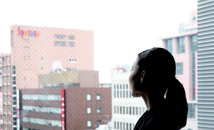 窓の外を見て思い悩む女性