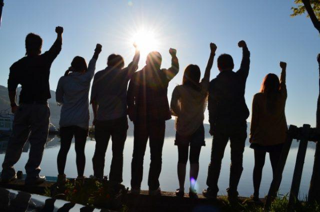 大学生が大人数で一緒に手を空に挙げている